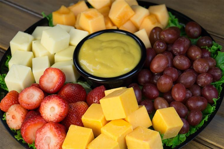 Fruit and cheese platter over a bed of lettuce with a dipping sauce