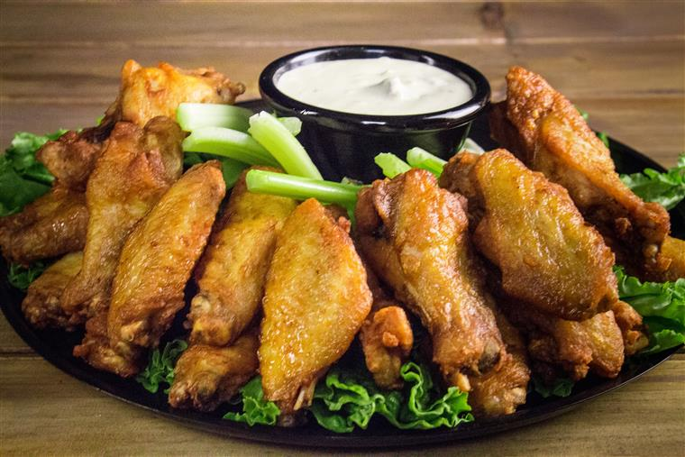 assortment of chicken wings with celery and dipping sauce