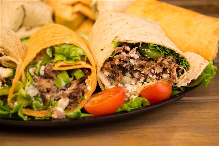steak wraps with lettuce and peppers on a tray with tomatoes
