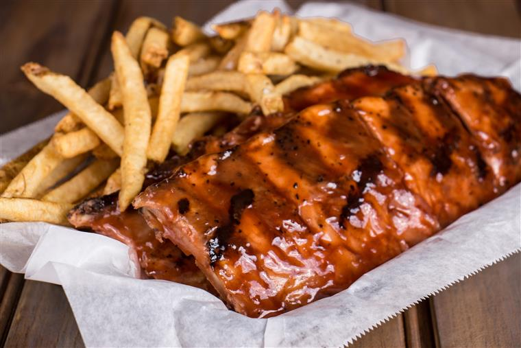ribs smothered in sauce with a side of fries
