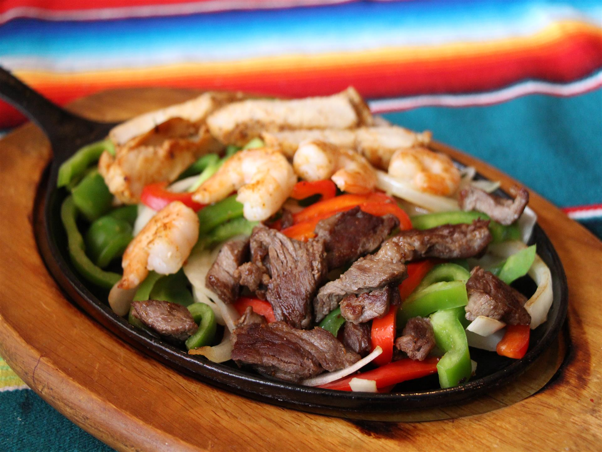 Fajita Skillet with Chicken, Steak and Shrimp on bed of Red and Green Peppers