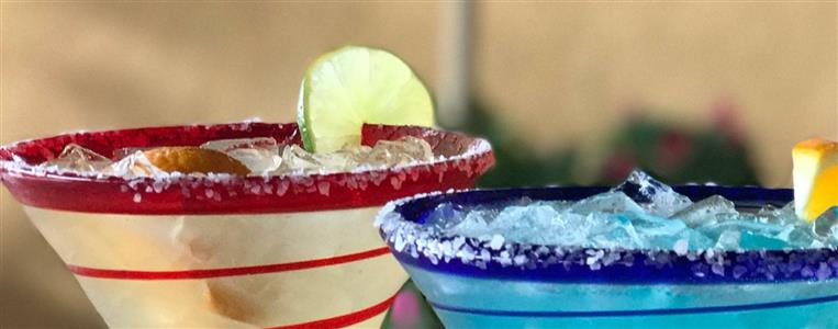 2 Margartias placed next to each other, salted and garnished with limes