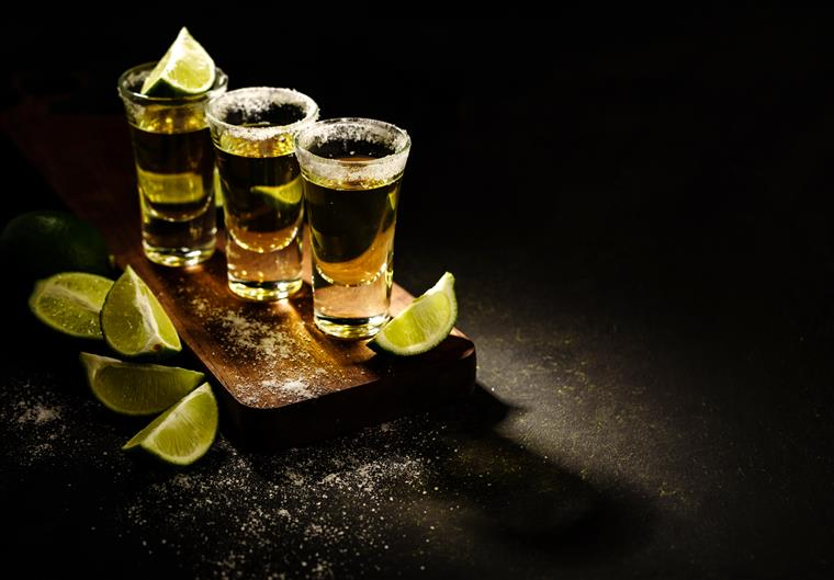 3 Shots of Tequila on table with salt and limes