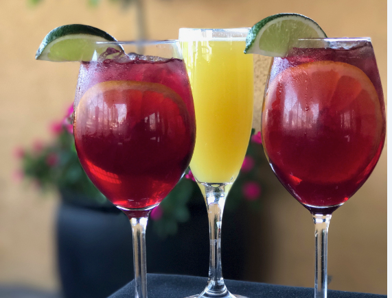 Two Red Sangrias placed in front of a Mimosa