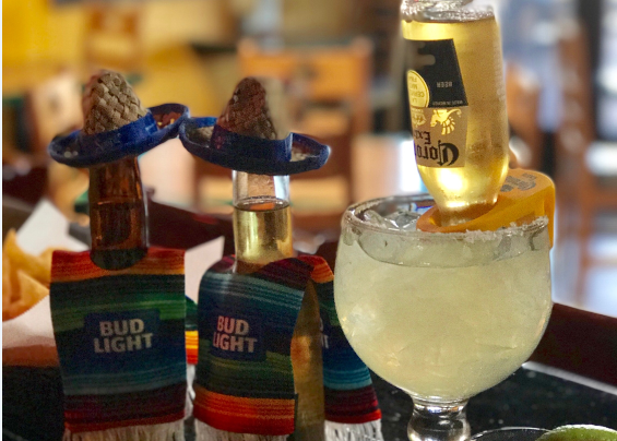 Two Bottles of Bud Light Lime wearing Bud Light Ponchos next to a salted Margarita (Coronarita)