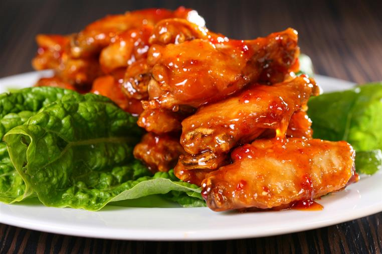 glazed buffalo wings on a bed of lettuce