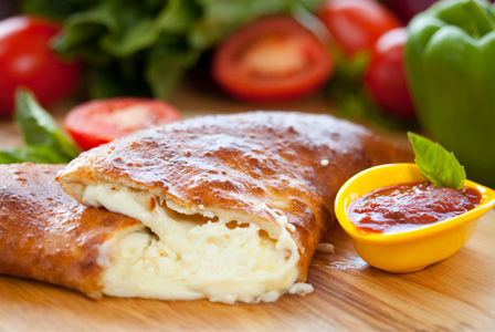 cheese stuffed calzone with a size of tomato dipping sauce