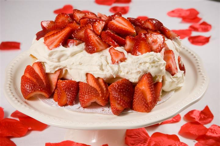 Cake topped with cream and strawberries