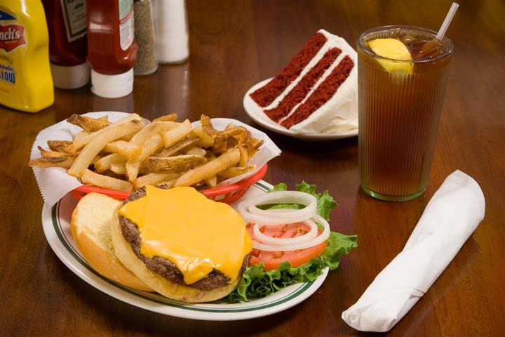 Hamburger and french fries with a side of red velvet cake alongside a glass of ice tea