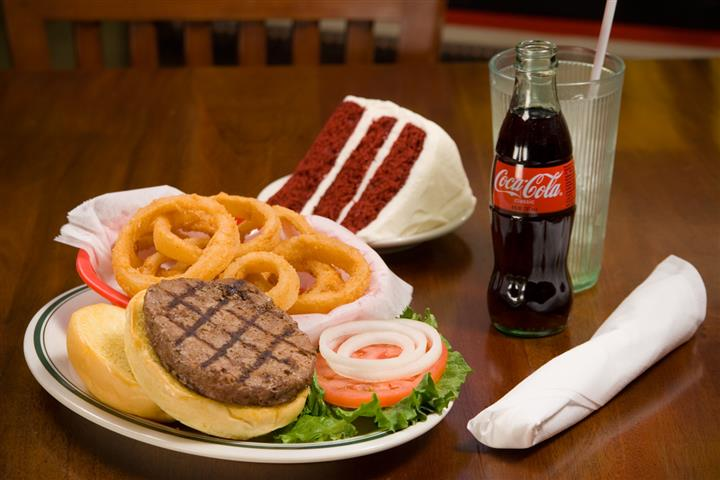 Hamburger and french fries with a side of red velvet cake alongside a coke