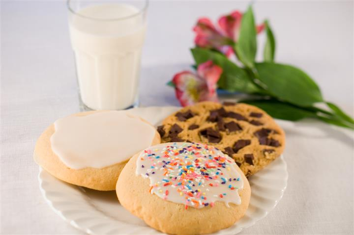 Assortment of different cookies with a glass of milk