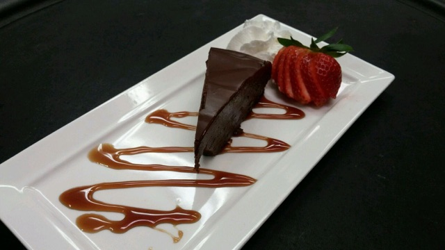 Slice of chocolate cake on a platter with a side of strawberry slices