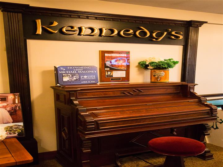 piano with a sign that reads kennedy's above it
