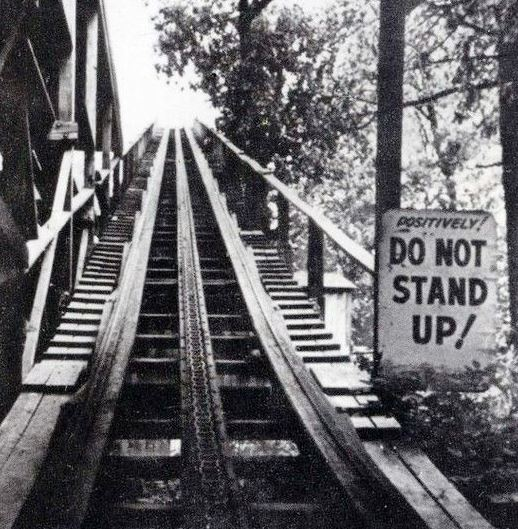 "Vintage photo of an old wooden roller coaster with sign saying ""DO NOT STAND UP!"""