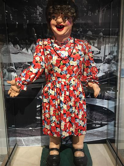 Statue of a women wearing a flower dress in a glass display case