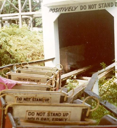 "Photo of roller coaster going into a dark tunnel withs signs that read ""Do NOT STAND UP HOLD RAIL FIRMLY"""