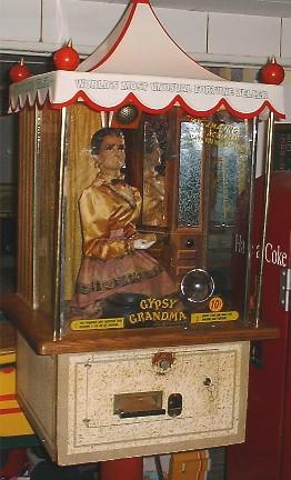 "Vintage attraction of a doll in a glass display names ""Gypsy Grandma"""