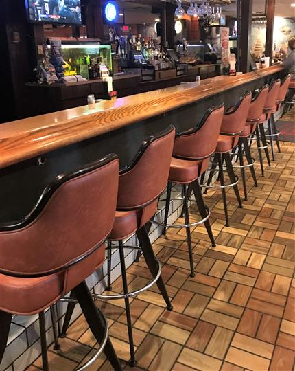 Empty barstool seats at a bar