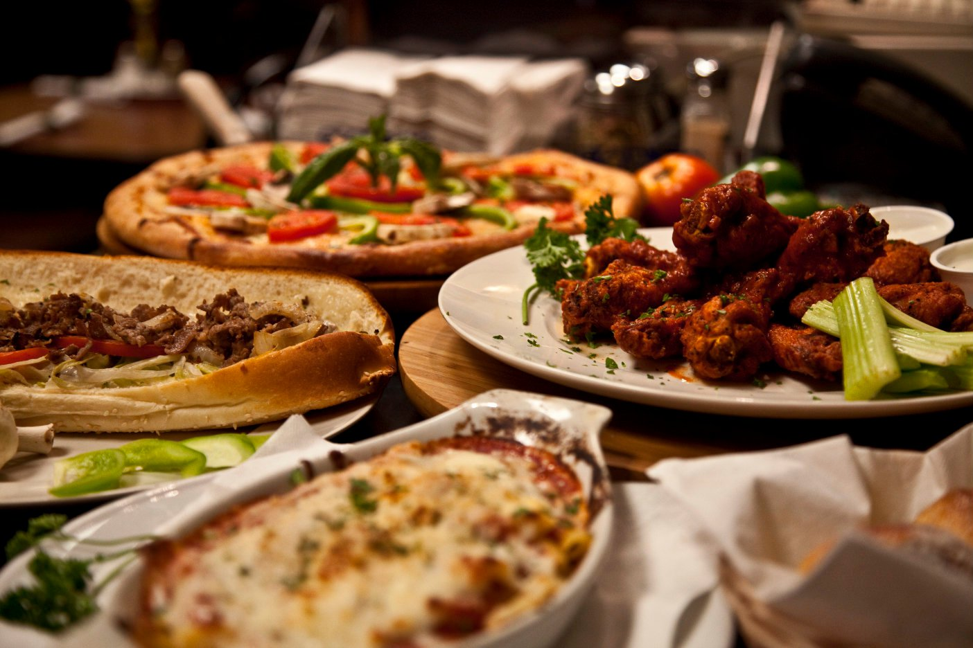 Table covered with dishes of food, a pizza platter, salads and more
