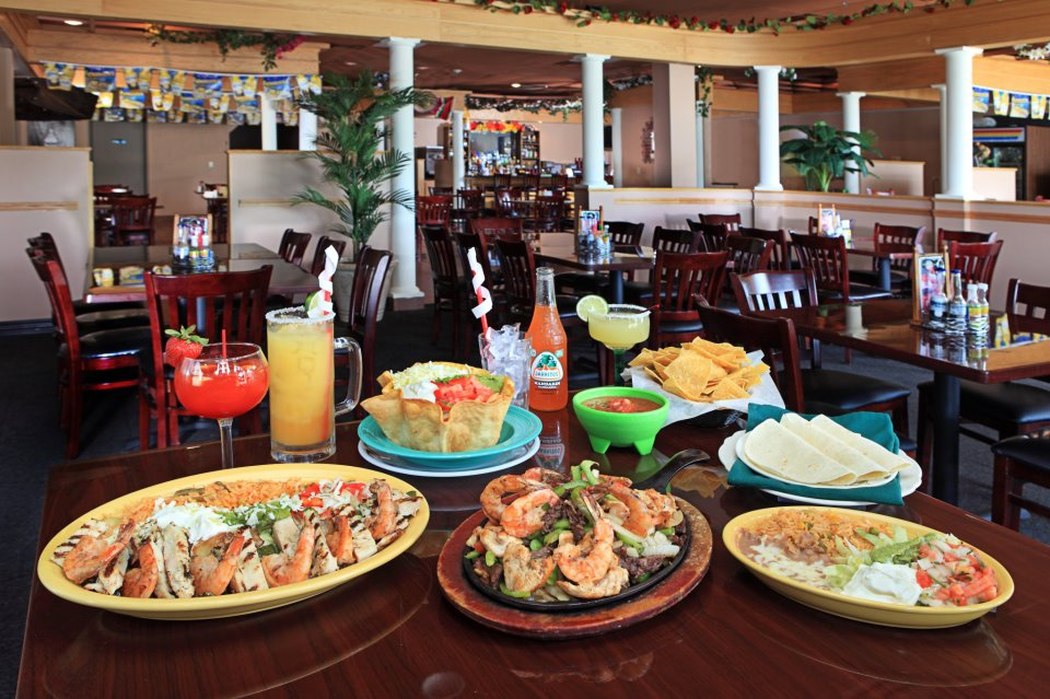 Variety of plates on table consisting of shrimp fajitas with egetables, rice, beans, and quesadillas