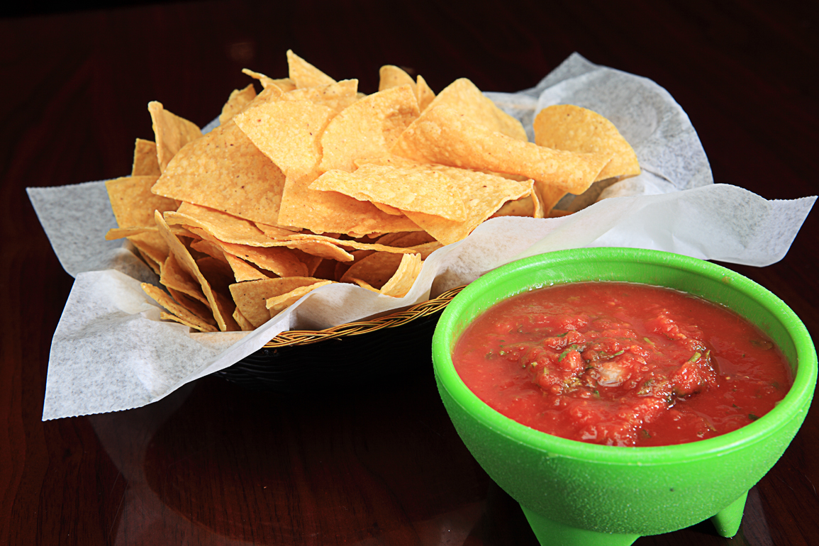 Tortilla chips in plate with cup of salsa