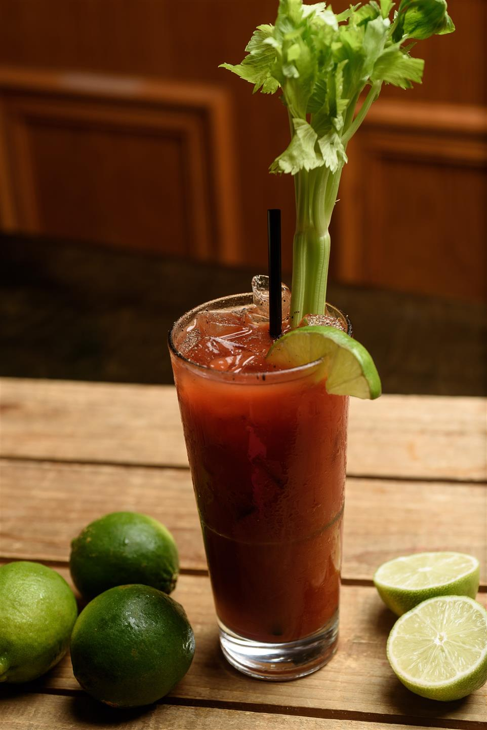 Bloody mary in glass with lime, celary, and black straw