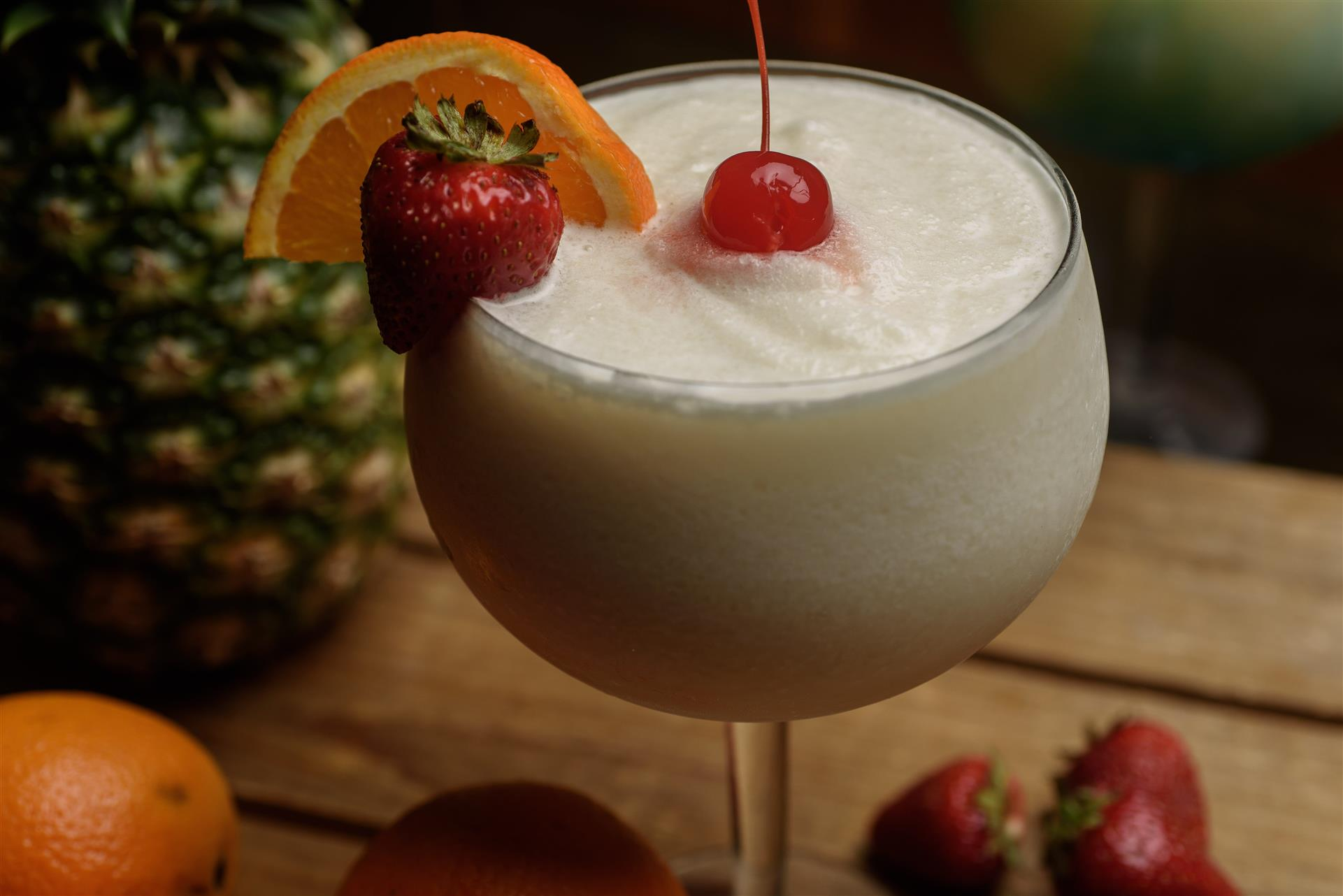 Beige colored drink in margarita glass with strawberry, lime, orange, and cherry