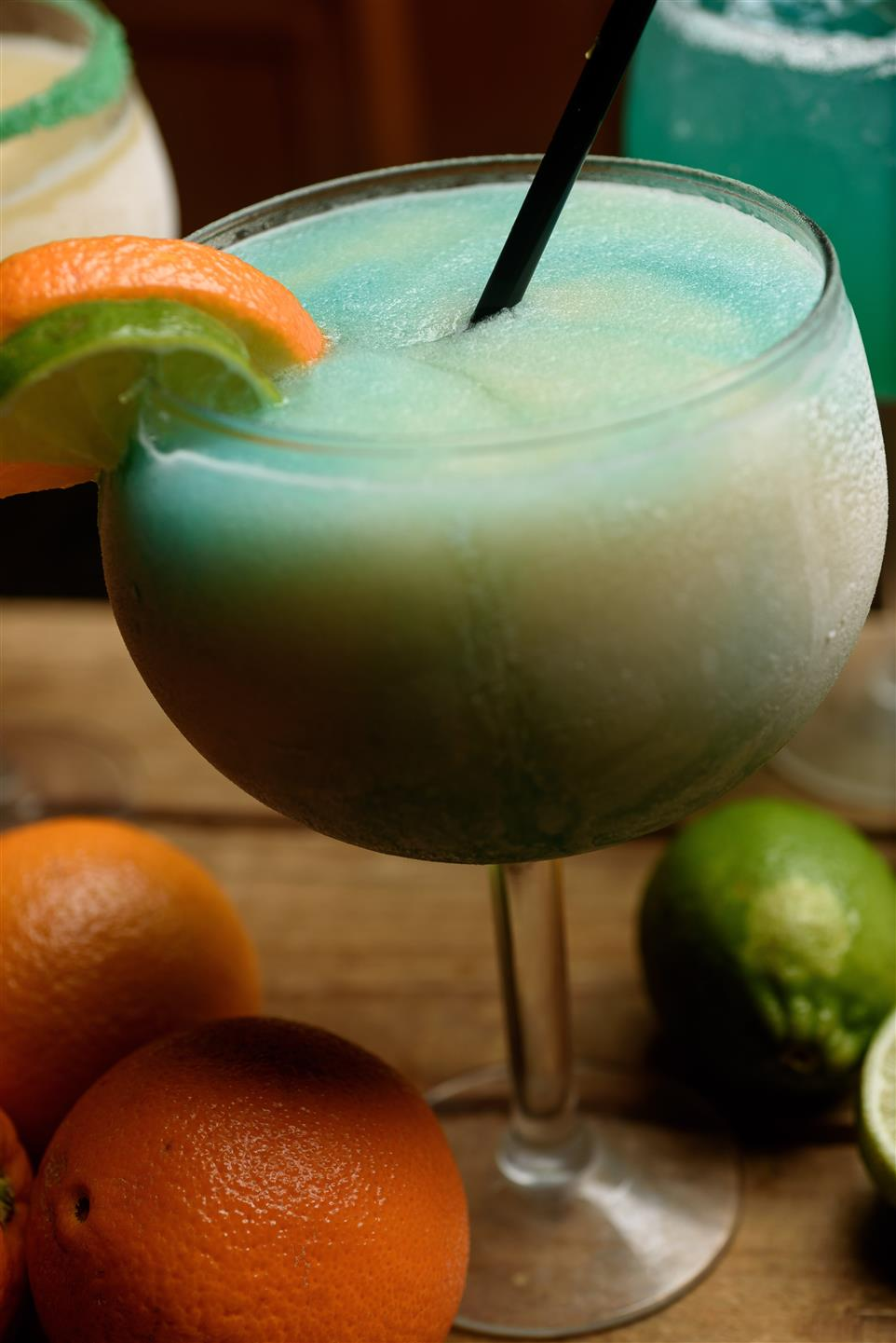 Beige and blue colored drink in margarita glass with lime and orange wedge