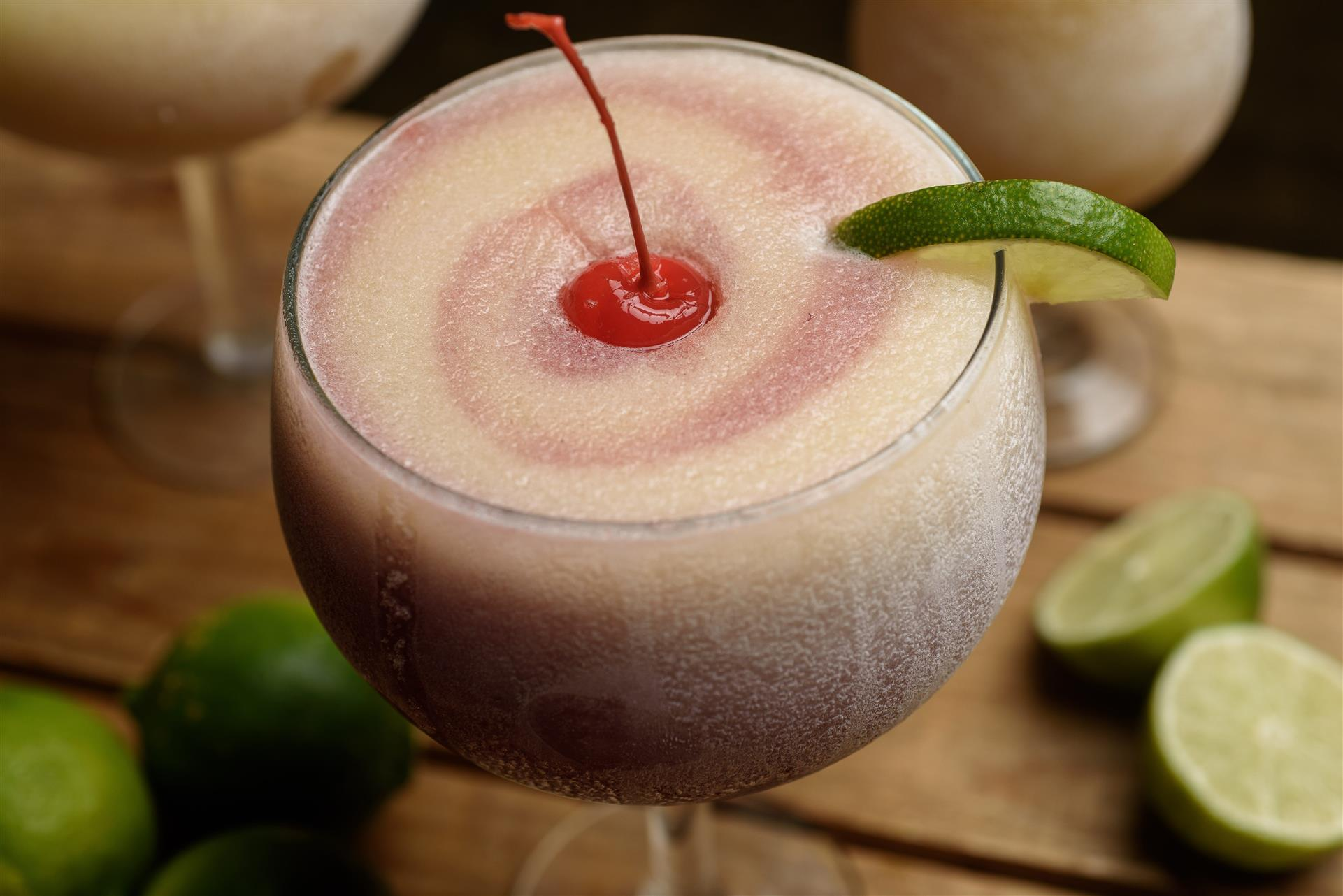 Frozen pink and yellow margarita with cherry and lime