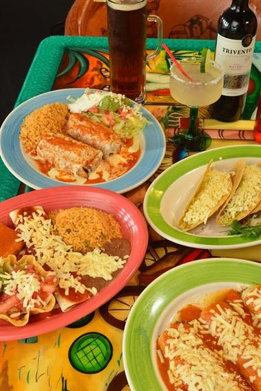 table with enchiladas, taco and drinks
