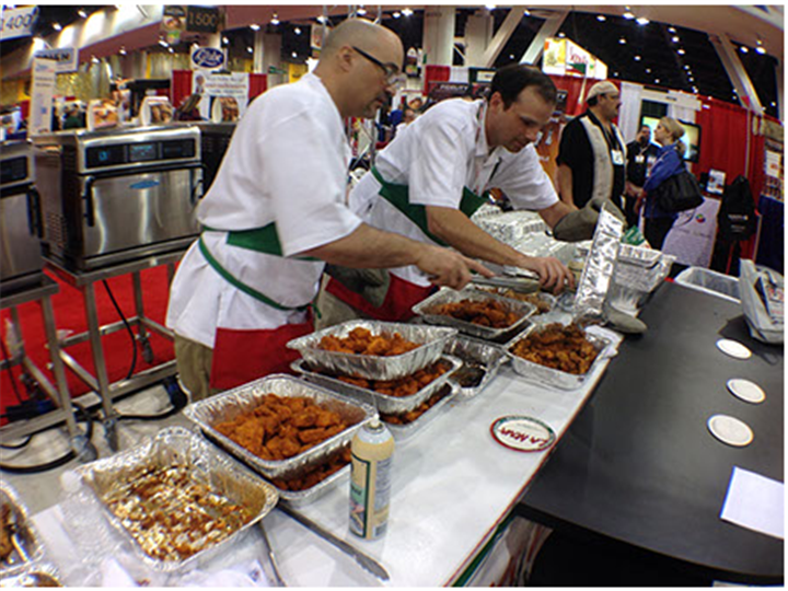 Chefs preparing wings at food show