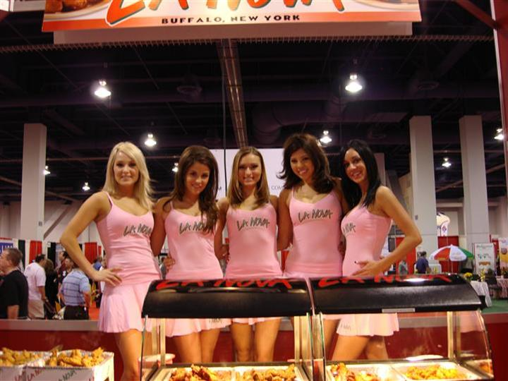 La Nova models posing for photo at food show behind chicken wings