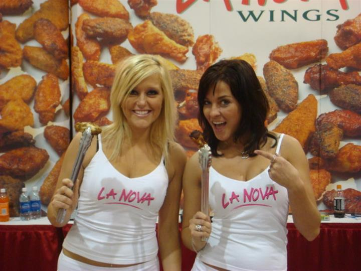 La Nova models holding chicken wings up with metal tongs