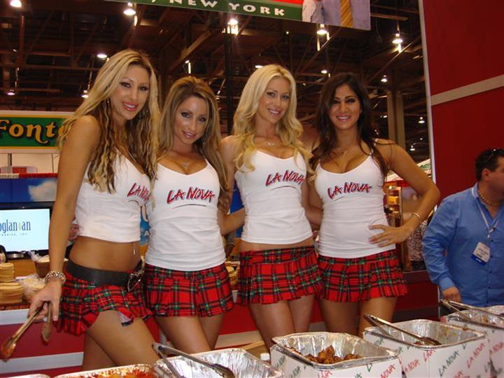 La Nova models posing for photo behind table of wings