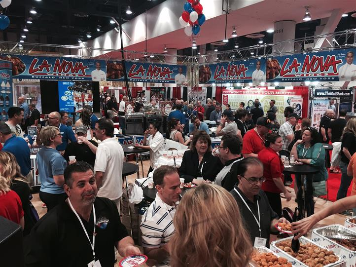 Crowd of people gather at La Nova Wings station of food show.