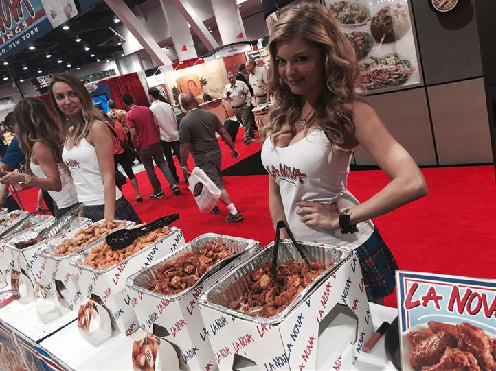 La Nova models behind chicken wing tables at food show