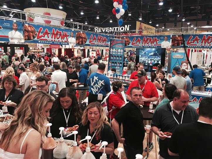 Crowds of people gathering for wings at la nova food station at trade show