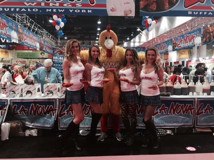 La Nova models holding chicken wings and posing with person in chicken costume.