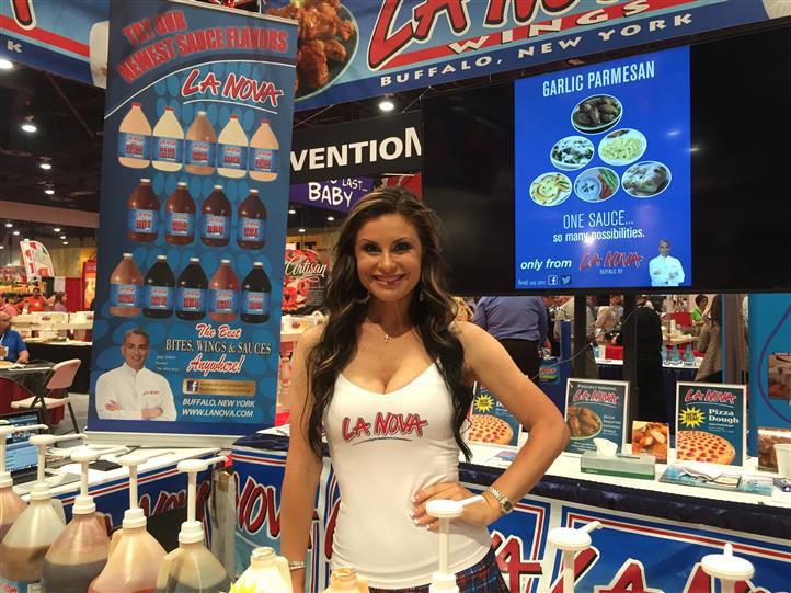 La nova model standing at table with jugs of la nova sauces.