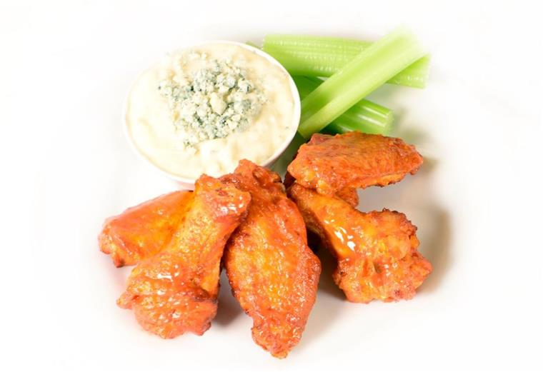 5 chicken wings tossed in hot sauce on a plate with celery sticks and bleu cheese dressing on the side.