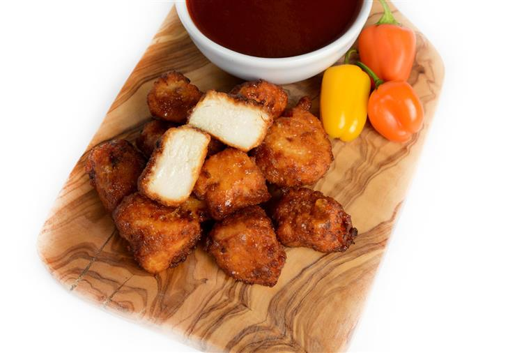 BBQ Boneless Chicken Bites on a wood tray with a cup of BBQ Sauce