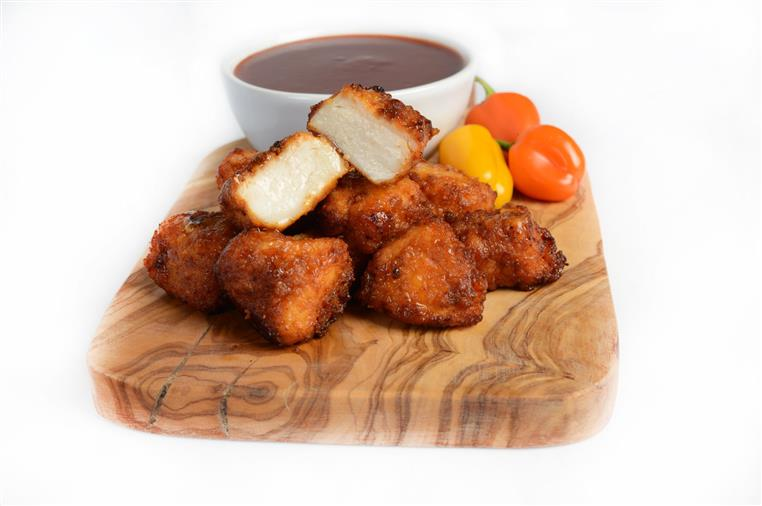 BBQ Boneless Chicken Bites on a wood tray with a cup of BBQ sauce on the side