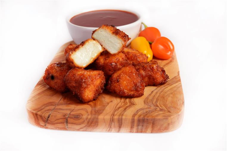Hot Boneless Chicken Bites on a wood tray with a cup of hot cause on the side