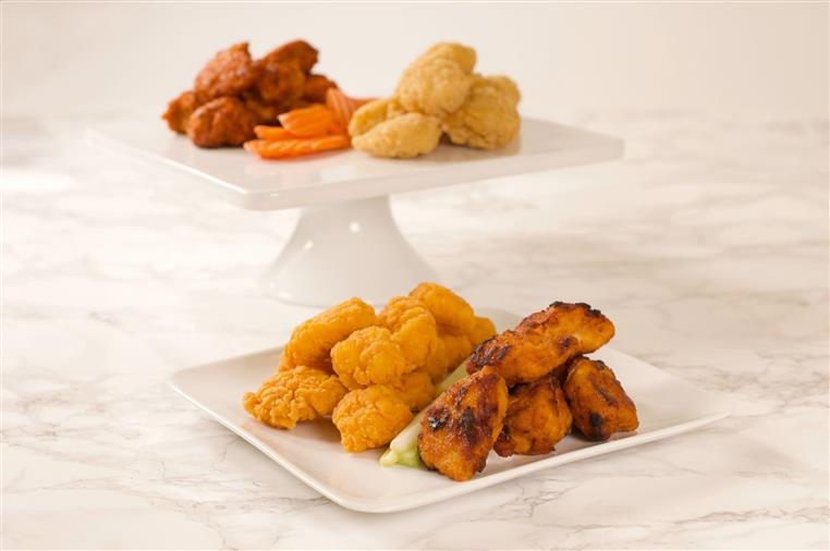 Chicken wings with assorted flavors on display with celery and carrots