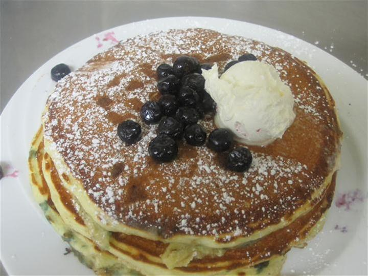 stack of panckes topped with blueberries and butter