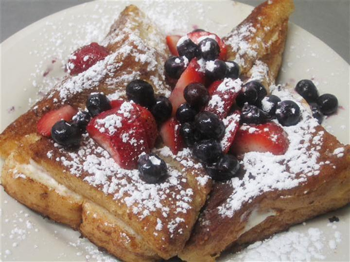 french toast topped with powdered sugar, strawberries and blueberries
