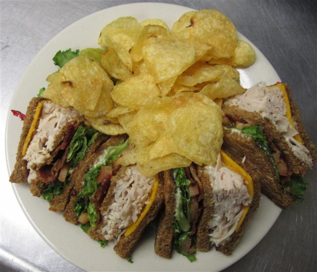 turkey sandwich cut in half with potato chips