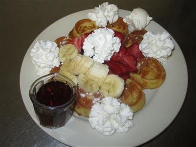 waffles topped with whipped cream, strawberries and bananas