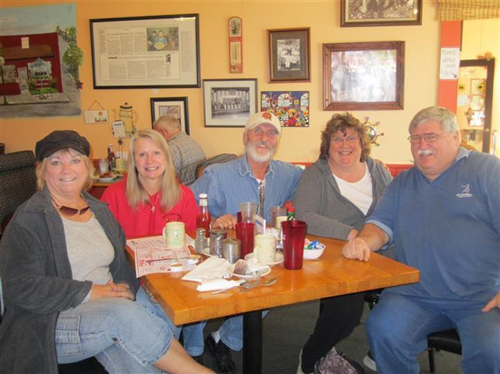 five people sitting at a table smiling
