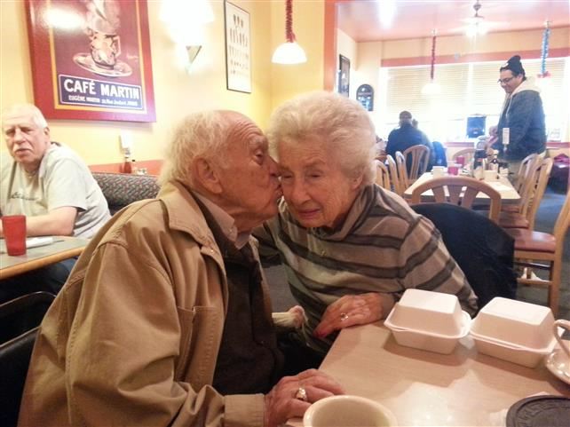 elderly man kissing elderly female